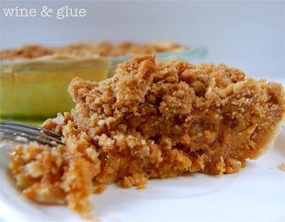 A slice of Dulce de Apple Streusel Pie which has a crumbly top and a light brown filling